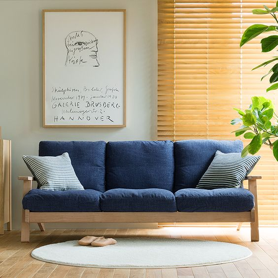 modern sofa with light wood frame and navy blue cushions round shaped rug wood window shutter