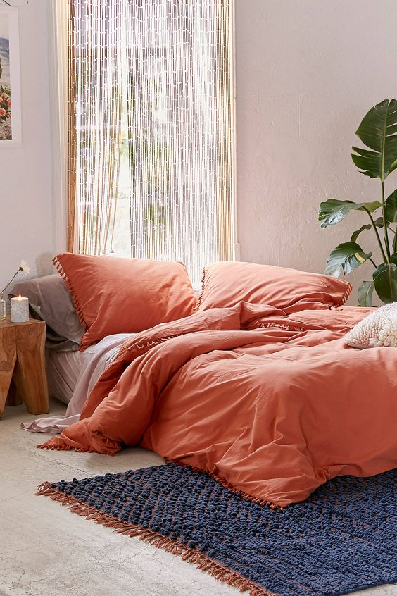 orange duvet cover with fringed tassels along the edges deep blue crochet rug with tassels macrame window curtains