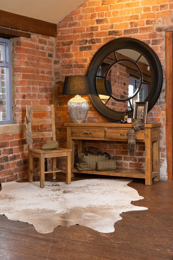 raw rustic dressing room wood table wood chair white cowhide barely red brick walls wood floors round top wall mirror with black metal frame