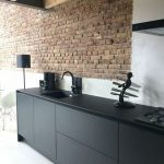 Red Brick Wall Highlight Featuring White Painted Walls Clean Line And Elegant Black Cabinets And Countertop