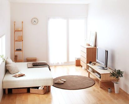 simple homey and minimalist bedroom light wood media console round shaped area rug in brown light wood dresser light wood floors light wood ladder rack