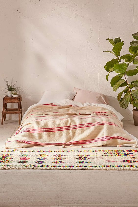 warm white duvet cover with red line accents white knitted runner with colorful accents potted houseplant wood side table for the greenery