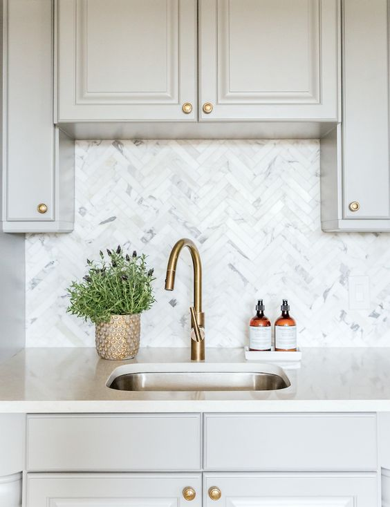 white kitchen cabinets whitewashed herringbone tiled backsplash potted herbs brass faucet stainless steel kitchen sink
