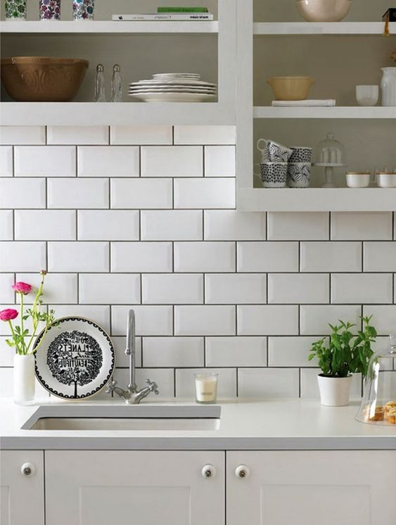 white subway tiled backsplash with dark grouts white kitchen countertop and cabinets ornate plate ornate potted herbs ornate potted flower