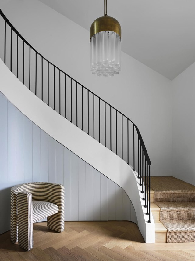 white wall panelling beneth the stairs contemporary chair herringbone patterned wood floors interior stairs