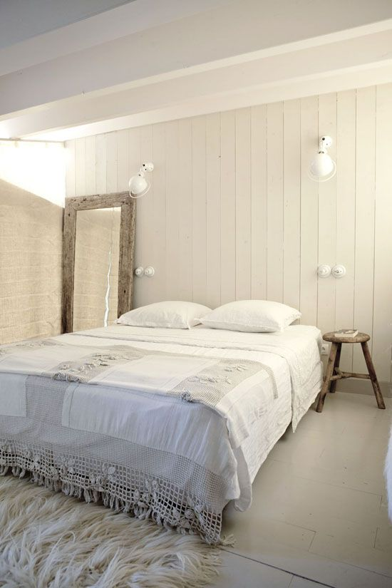 white wood plank walls white floors white shag rug a couple of wall mounted bedroom lamps shabby wood framed mirror shabby wood side table