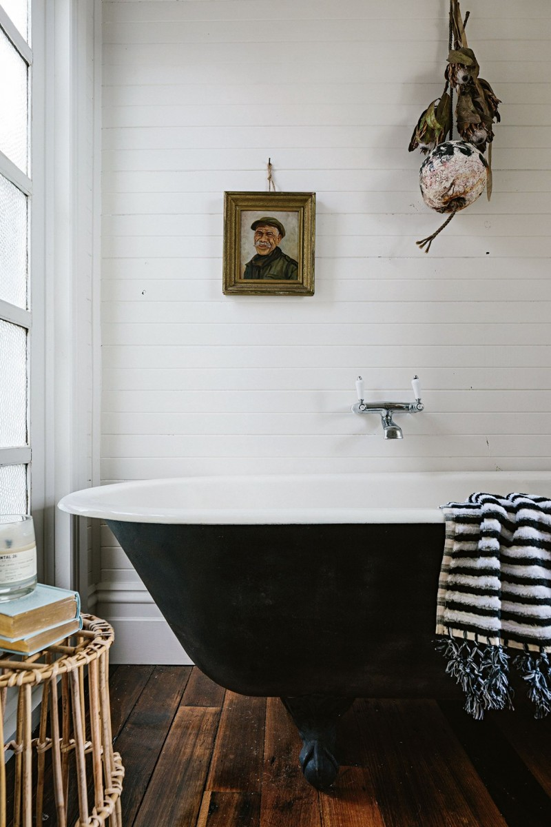white wood wall panelling claw foot bathtub with black finish dark wood plank floors