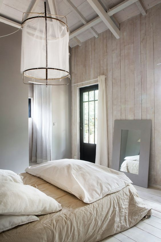 whitewashed wood plank walls oversized pendant with white transparent textile lampshade cream bed linen white pillows and blanket gray framed mirror