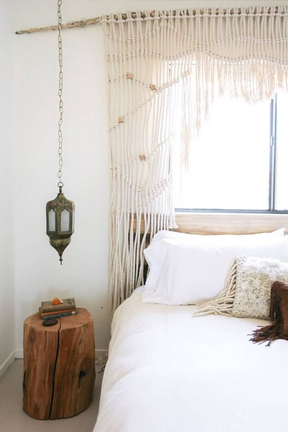 window with macrame draperies Moroccan inspired ceiling lamp tree trunk bedside table white bed linen