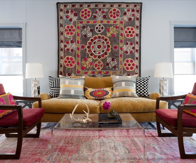worn out area rug clear acrylic coffee table mustard sofa magenta chair with wood frame large textile wall decor as the focal point