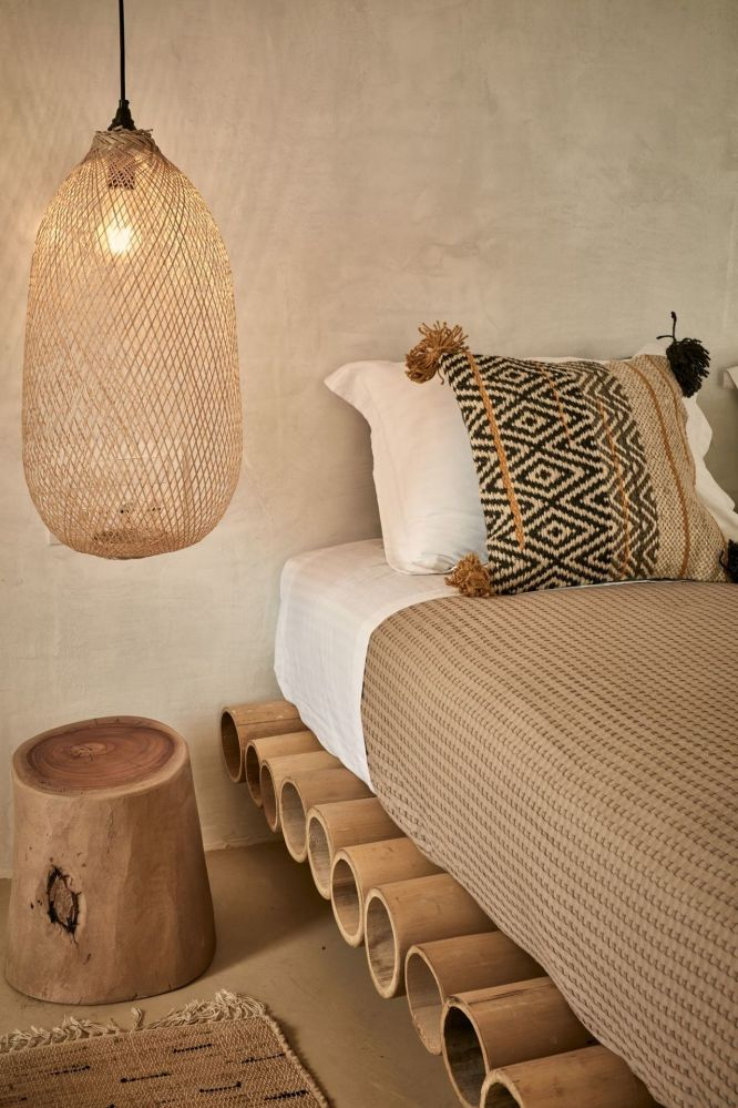 bamboo bed frame white bed linen textured bed linen in warm beige ethnic print pillow log bedside table pendant with oversized handcarved woven bamboo