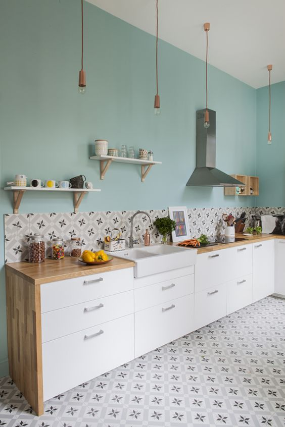 clean look and minimalist kitchen clean blue walls accented with some series of open shelving units wood top countertop flower motif tile backsplash and floors white cabinetry