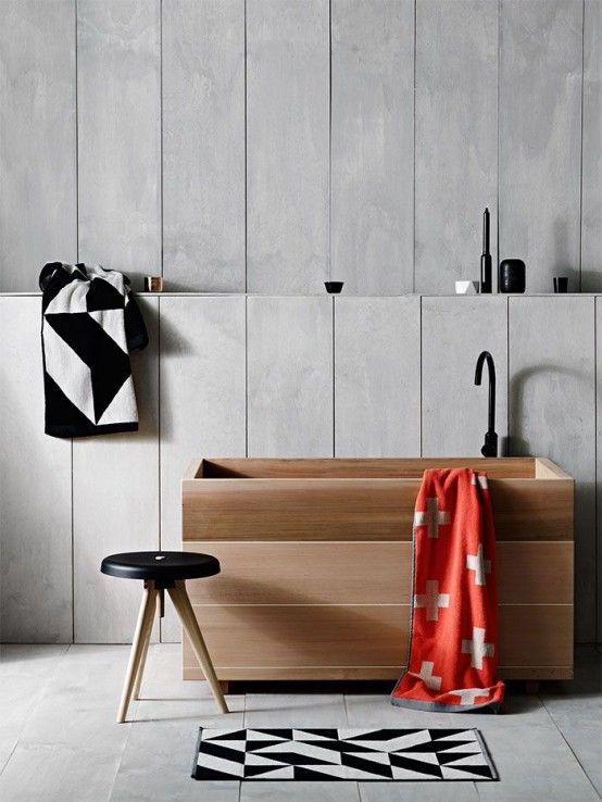 gray washed wood plank walls gray tiled floors modern stool with round black leather top and angled wood legs wooden bathtub bathroom mat in black and white