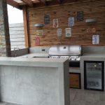 Industrial Minimalist Outdoor Kitchen Idea Concrete Tiled Floors Concrete Kitchen Counter Wood Plank Walls Stainless Steel Utensils