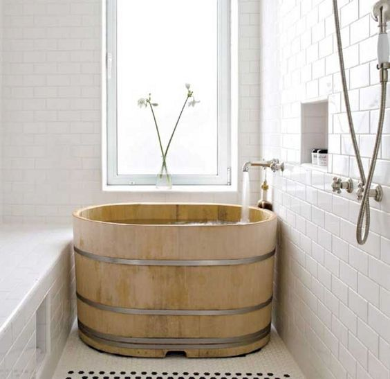 japanese soak tub made of wood center glass window white tiled walls white mosaic tiled floors recessed shelving unit