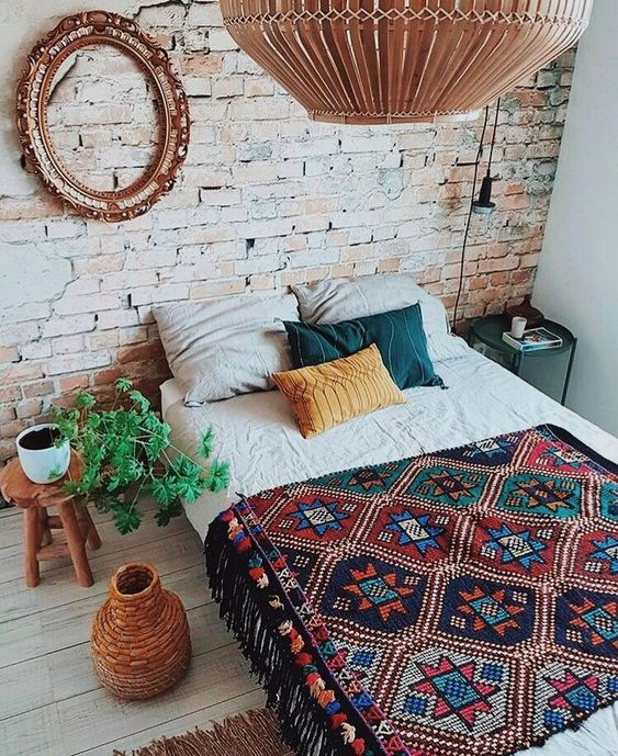 modern Bohemian bedroom design white bed linen ornate blanket with ethnical patterns and fringed tassels oversized pendant round top side table ornate vase carved wood frame