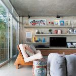 Modern Industrial Living Room Bare Concrete Walls To Ceilings Wooden Chair Wooden Media Console Concrete Open Shelving Units Colored Side Table