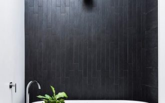 modern minimalist bathroom design black tiled walls light black tiled floors modern white bathtub wooden stool small greenery on white pot