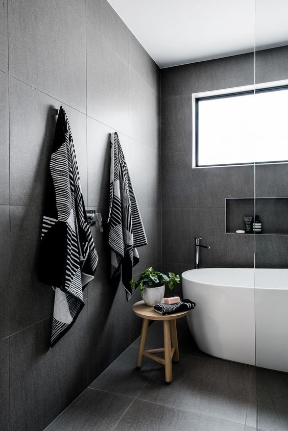 modern white bathtub light wood stool dark gray tiled walls and floors recessed shelving unit