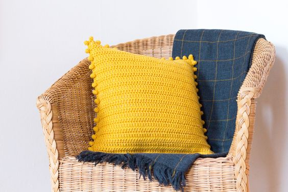 rattan chair with mustard throw pillow accented with pom poms deep blue throw blanket
