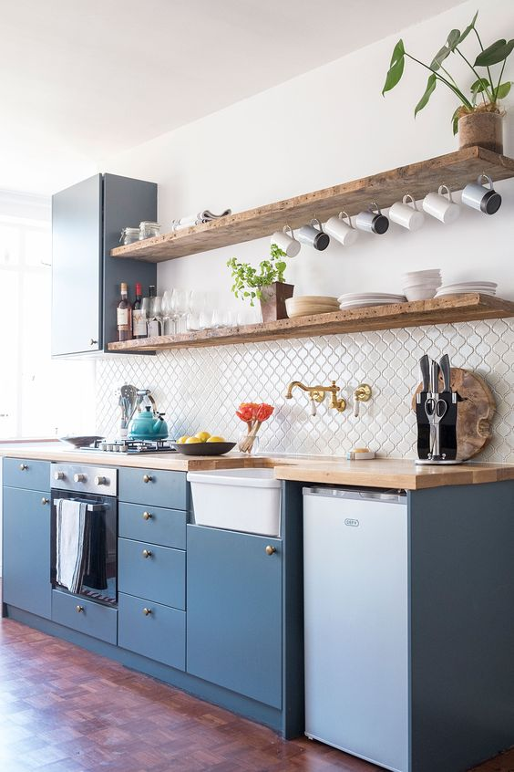 reclaimed wood shelves diamond cut tiled backsplash in white blue matte kitchen cabinetry clean white walls