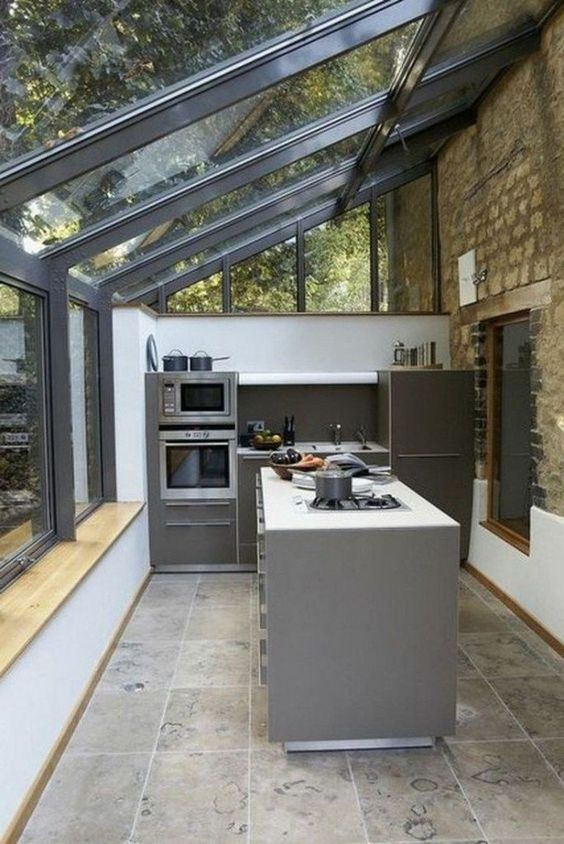sophisticated kitchen design glass roofs with metal trims small kitchen island in gray small kitchen counter and cabinetry in gray worn out brick walls concrete like tile floors