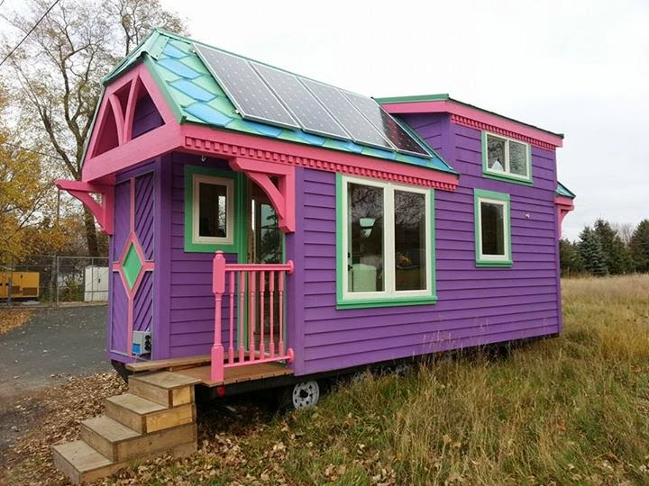 tiny house with pink purple and teal exterior color hues plus some solar panels