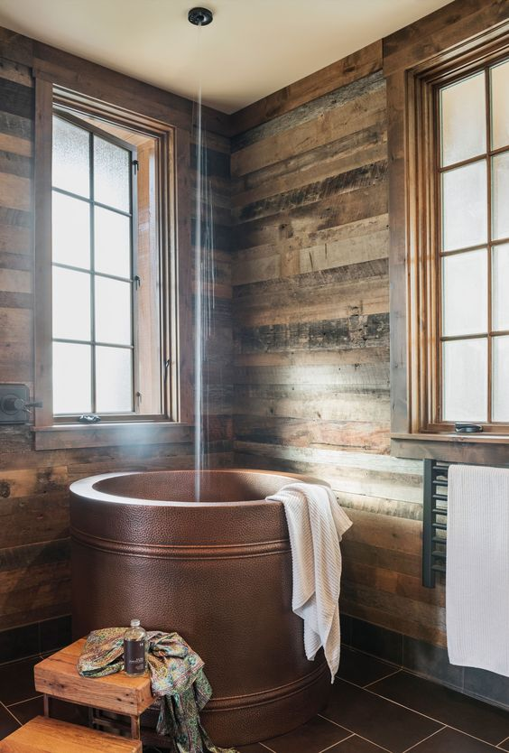 traditional japanese soak tub made of metal handmade wooden stairsteps dark toned wood plank walls