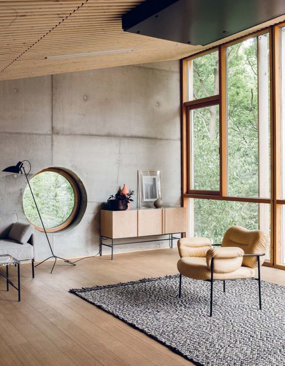 warm modern industrial interior design exposed wood ceilings modern chair with cozy cushion flat woven wool rug in gray light wood floors glass windows with wood trims round shaped accent window