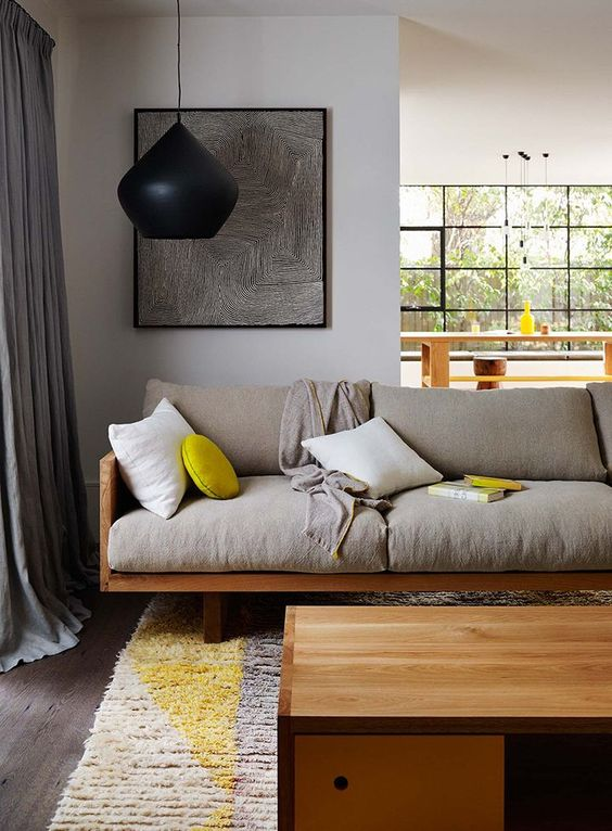 wood framed sofa with light gray cushions gray area rug oversized pendant with black lampshade