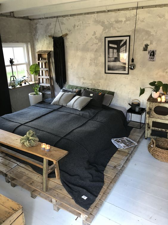 wooden platform bed frame black linens for bed wooden bench bed bare concrete wall some greenery