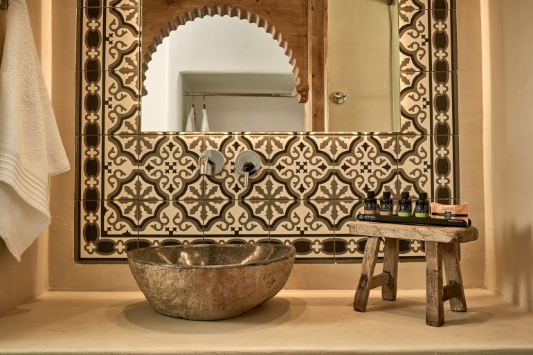 wooden stool on the countertop stone like sink vanity mirror framed with classic print tiles
