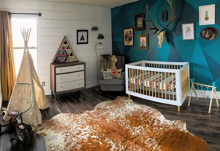 Boho chic nursery room cowhide area rug white baby crib bold geometric wall wood plank wall in white ornate american tribal tent dresser gray nursery chair