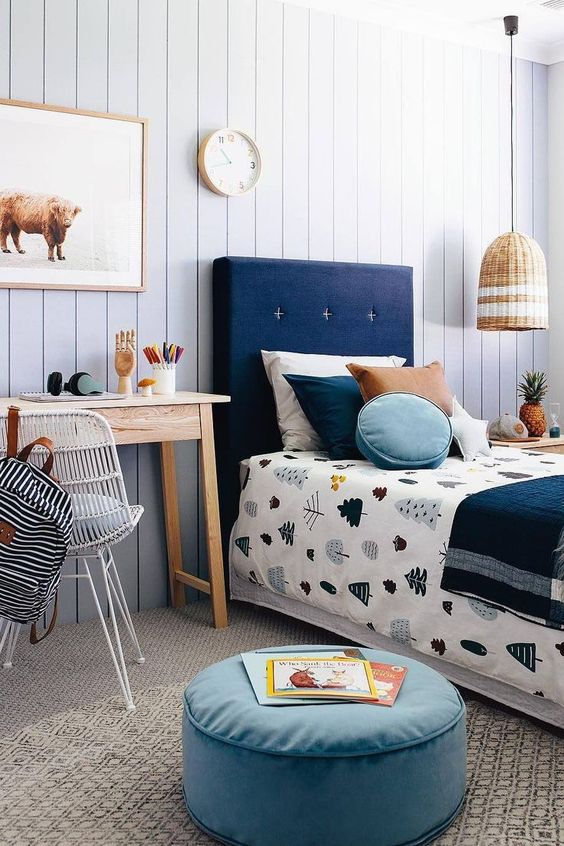 Scandinavian style boy's room single bed frame with higher blue headboard light blue pouf wooden console table wire chair in white oversized pendant