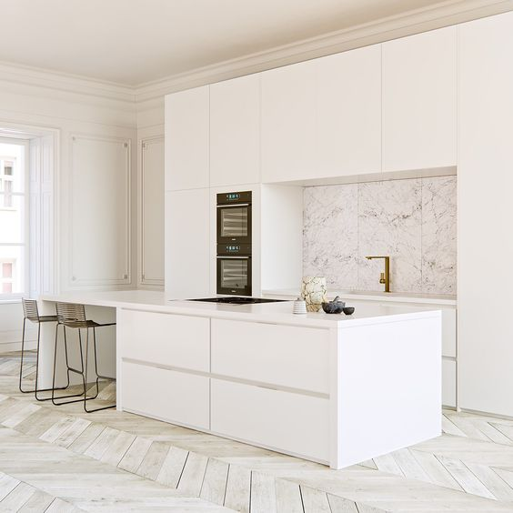all white kitchen island and mini bar white cabinetry marble splashback gold toned faucet white washed wood plank floors in herringbone pattern