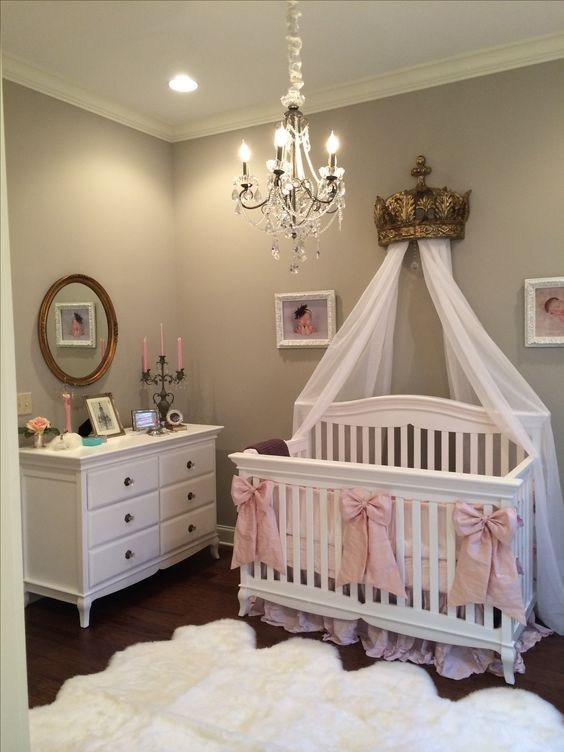 baby girl nursery room white crib with pink ribbon ornaments white curtains and ornate gold tone crown white dresser white shag rug