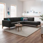 Black Modular Sofa With Tapered Wood Legs Round Top Coffee Table Made Of Wooden White Area Rug Wood Floors Crisp White Walls