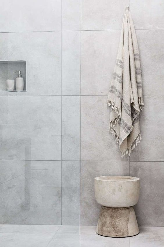 cool and minimalist bathroom white tiled walls and floors recessed shelving unit light wood stool