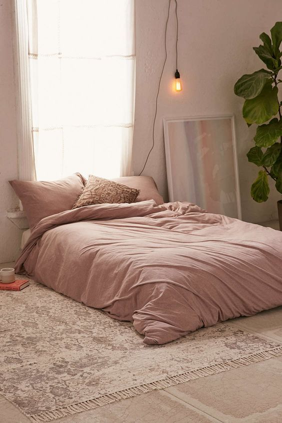 dusty pink duvet cover and pillows worn out area rug with fringed trims houseplant
