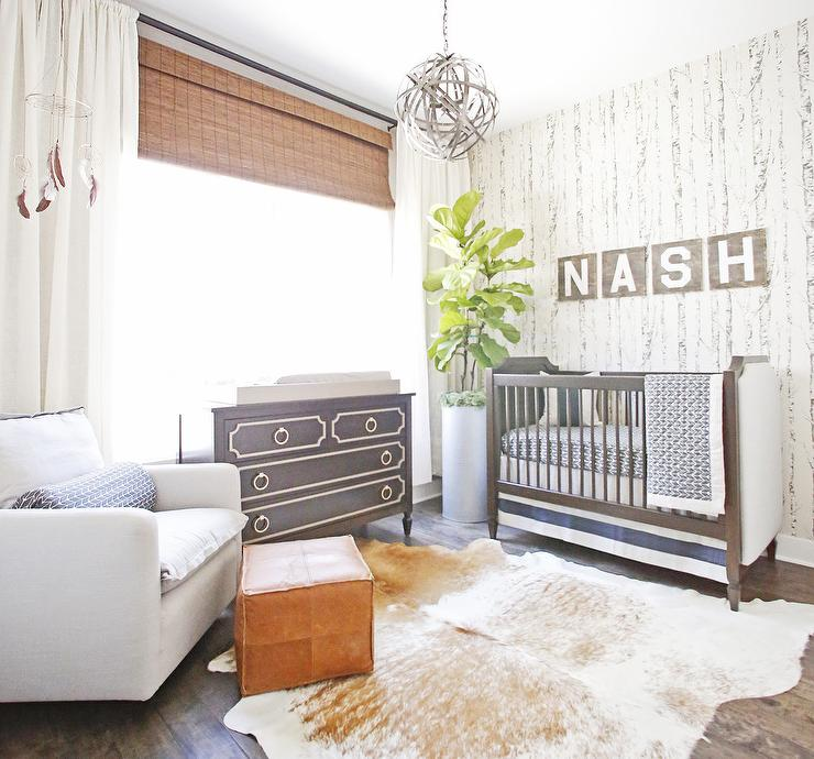gender neutral nursery room in chic and clean look cowhide area rug white nursery chair leather like finish feet rest black dresser black baby crib houseplant on pot