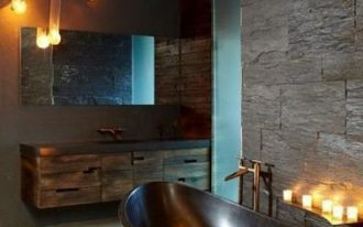 glossy black bathtub stainless faucet black stone walls dark wood vanity cabinets frameless mirror warm toned lighting fixtures
