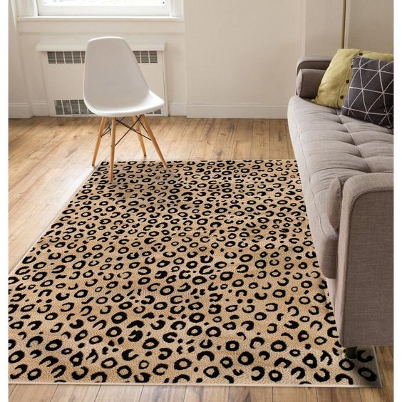 leopard print area rug midcentury modern chair in white modern sofa in gray wooden plank floors
