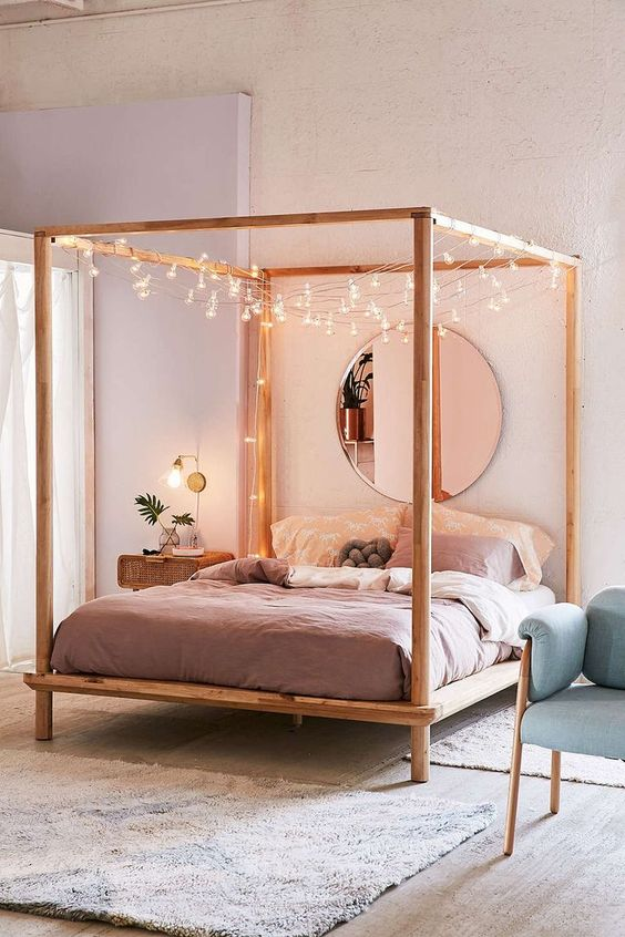 minimalist bedroom idea wood bed frame with DIY wood canopy garnished with string lamps light purple duvet oversized round wall mirror white area rug