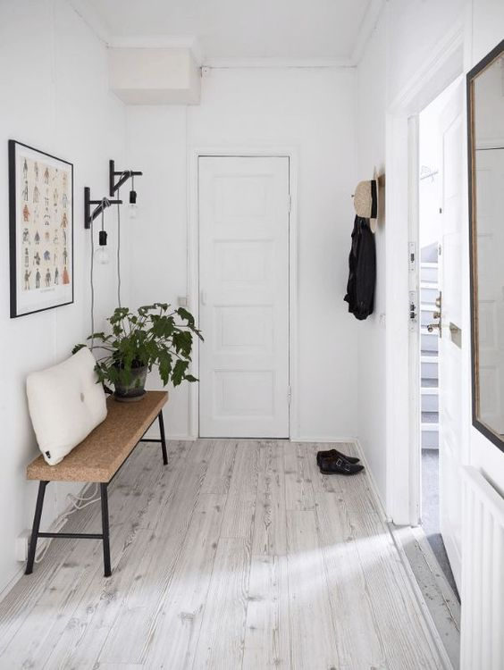 minimalist hallway idea super light wood floors wood bench seat with black iron legs throw pillow in white crisp white walls and door