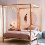 Modern Boho Bedroom Idea Solid Wood Bed Frame With Canopy And Ornate String Lamps Over The Bed White Rug Round And Frameless Wall Mirror In Large Size