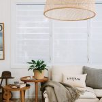 Oversized Rattan Pendant For Boho Touch White Sofa With Throw Pillows And Throw Blanket Round Top Side Tables Made Of Wood