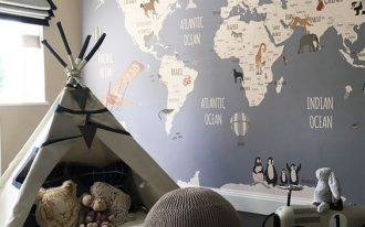 playroom in kids' room teepe some animal stuffs gray pouf flat woven rug in white world map wall decal