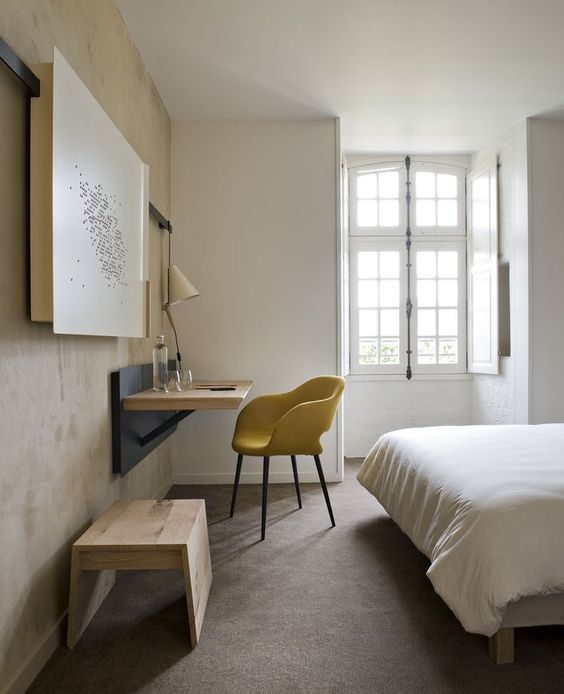 pop of yellow chair in midcentury modern style wall mounted working table light wood bench seat white bed linens gray floors white walls