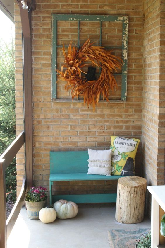 small bench seat with back in blue log side table red brick walls ex window trim wall decor with dried leave wreath in the center