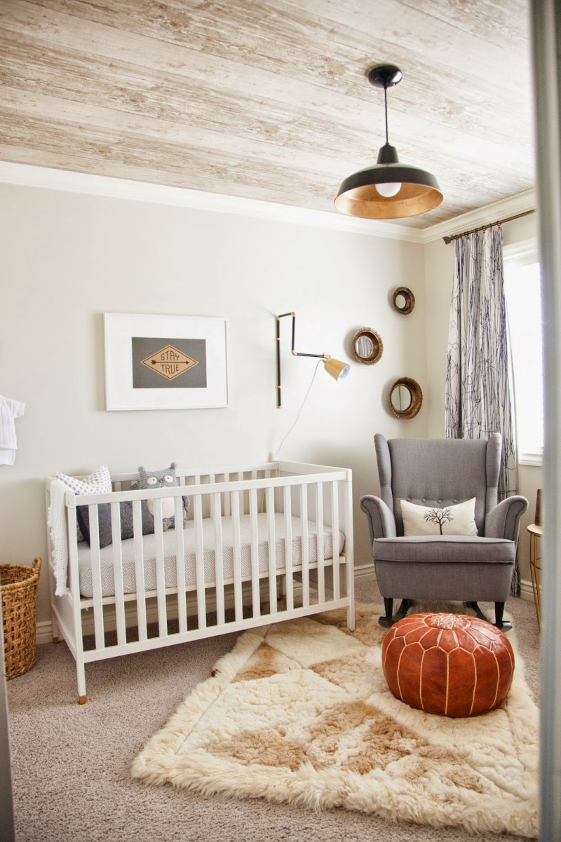 woodprint wallpaper on ceiling crisp white walls white baby crib light brown shag rug brown pouf gray nursery chair